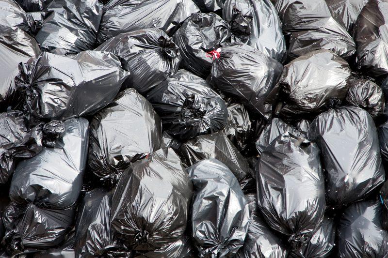 black garbage bags filled stacked 0